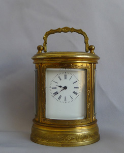 Antique miniature French oval, engraved carriage clock.