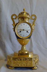 Antique French Empire patinated bronze and ormolu vase clock dated 1810.